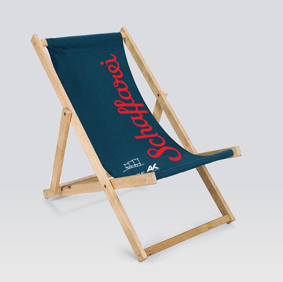 Strand-Liegestuhl des Schaffarei Festivals der AK Vorarlberg mit blauem Stoff und rotem Schriftzug.