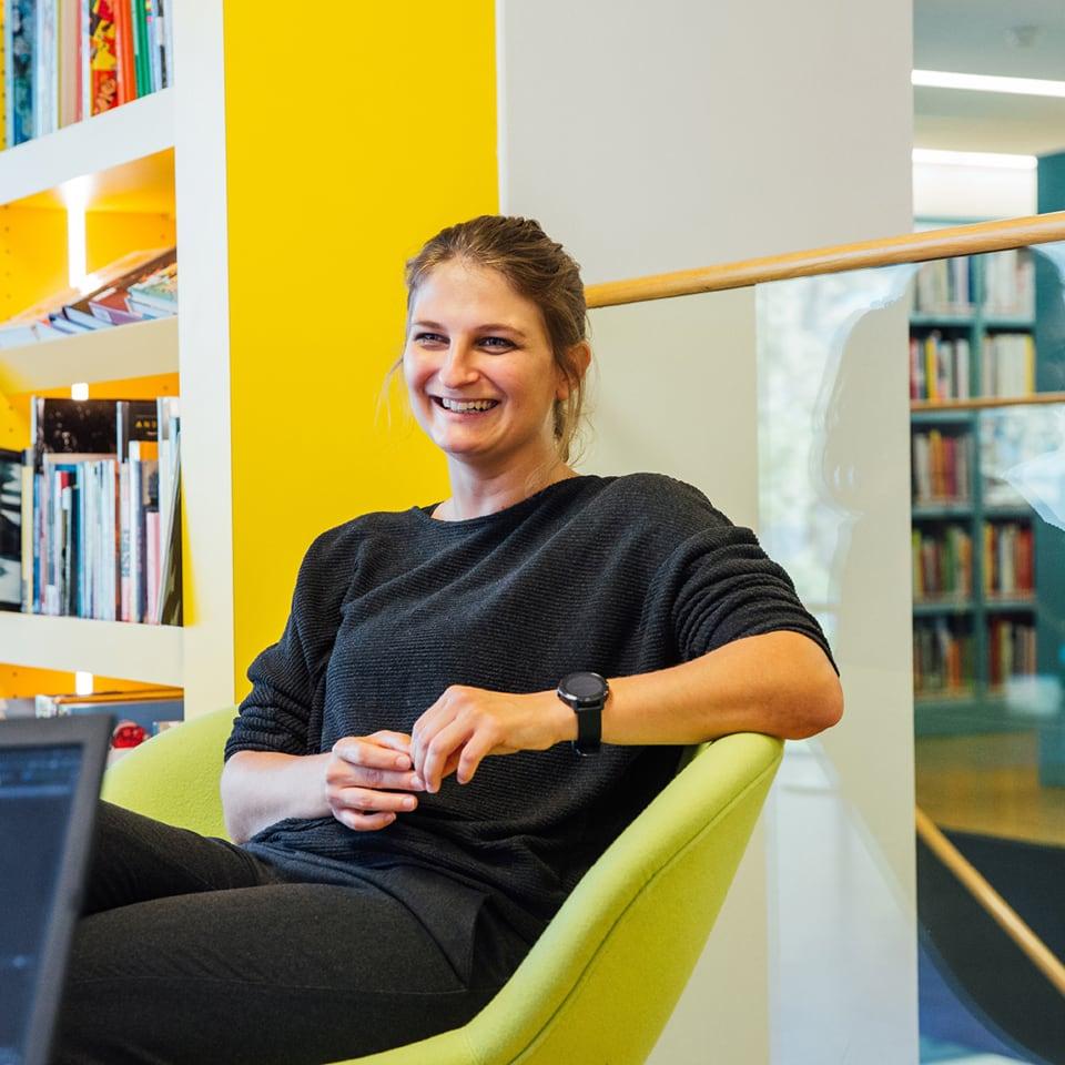 Junge Studentin sitzt in grünem Loungechair