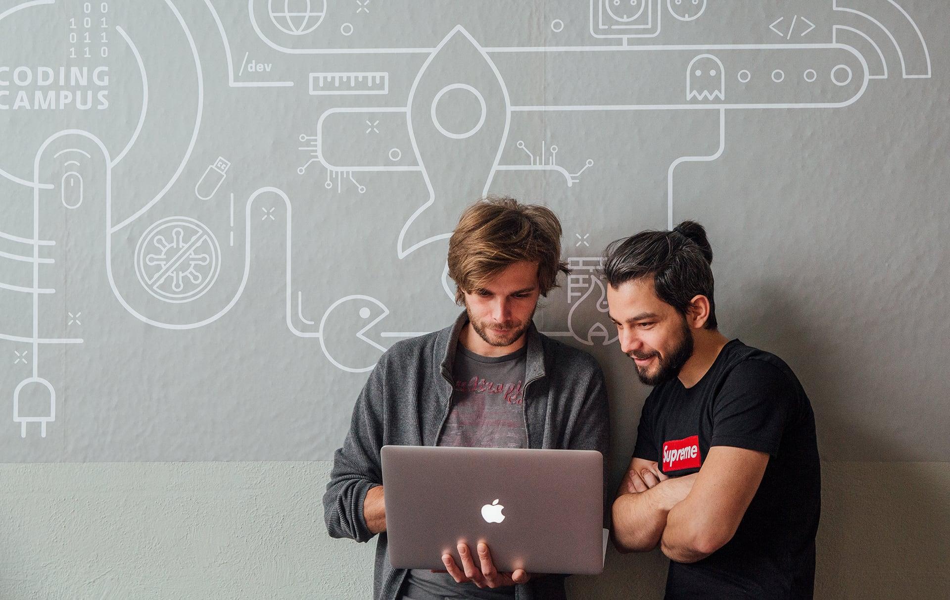 Zwei junge Studenten stehen mit Laptop vor gestalten Innenwand im Campus