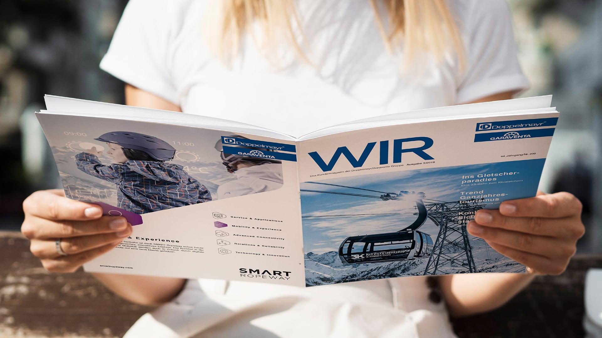 Frau hält Magazin WIR - Cover