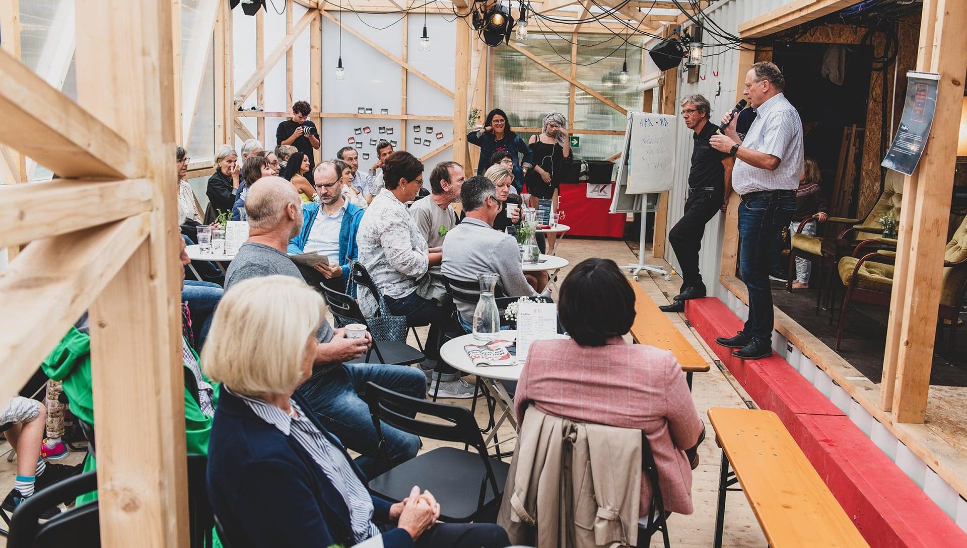 AK Präsident Hubert Hämmerle spricht zum interessierten Publikum im mobilen Schaffarei Gebäude.